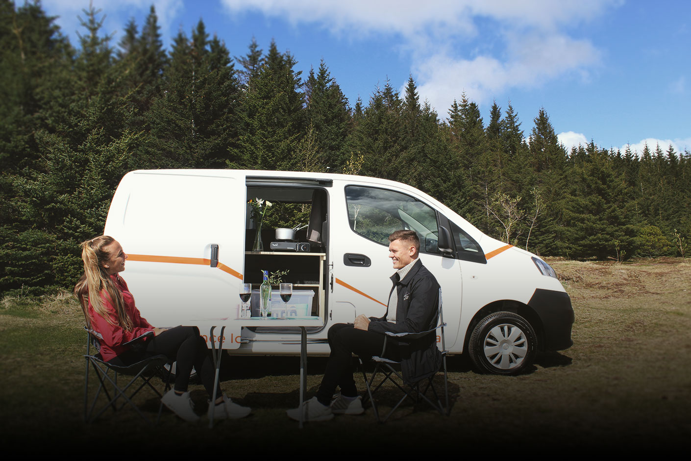 Couple Drinking Wine outside a White Camper Van with Pine Trees in the Background