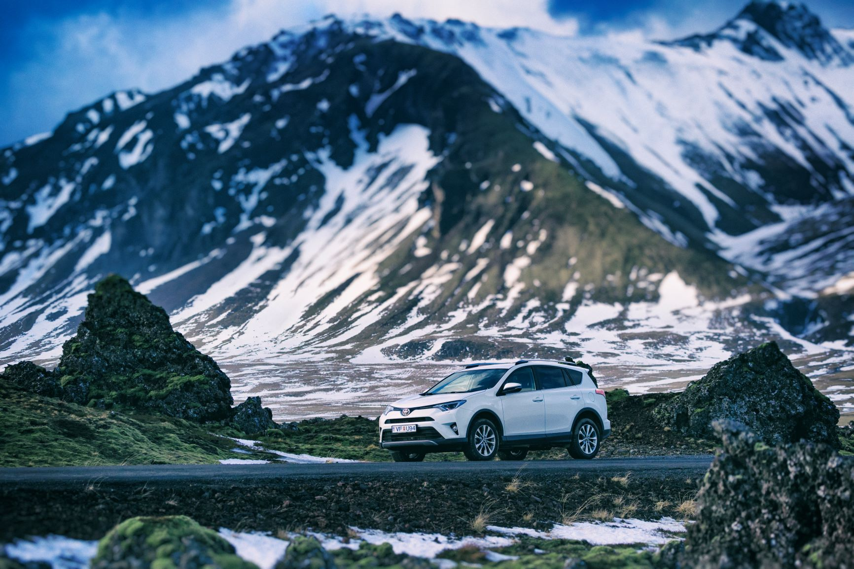 White Toyota Rental with Snowy Mountain Range Background