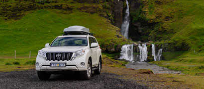 White Toyota Rental SUV and Silver Roof Box with Waterfall and Green Mountain